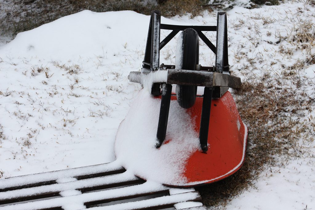 an orange wheelbarrow partially covered by snow in a spring snowstorm